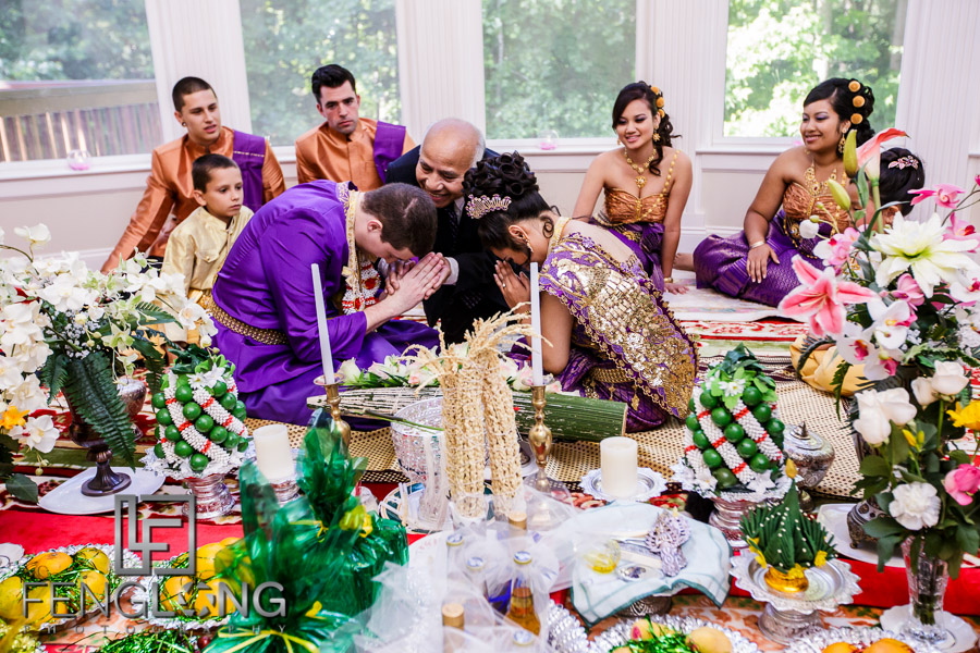 Bride and groom light candle during Cambodian wedding ceremony