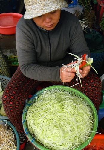shredding green papaya in the market in Hoi An