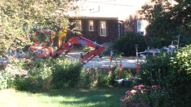 hole in street in front of driveway and machinery