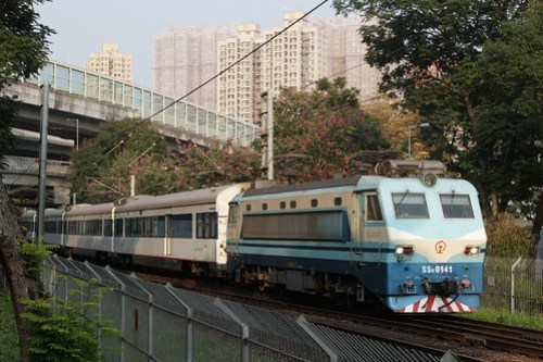 China Railways electric locomotive SS8 0141 leads a consist of type 25T carriages southbound at Tai Wai