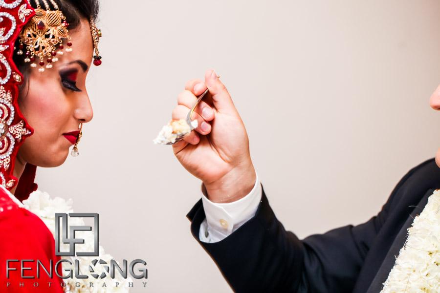 Groom feeding cake to bride