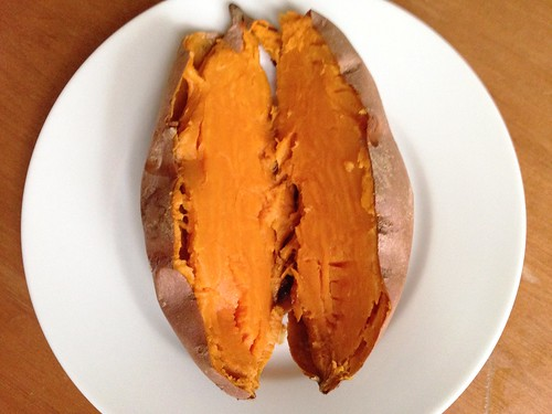 splitting open a baked sweet potato