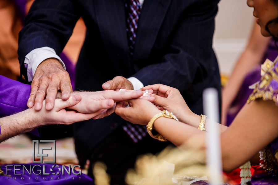 Bride and groom exchanging rings during Cambodian wedding ceremony