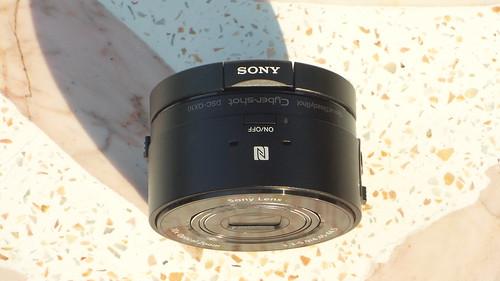 Sony Cybershot QX-10 ด้านบน มีโลโก้ Sony มีไมโครโฟนสเตริโอ ปุ่มเปิดปิด แล้วก็สัญลักษณ์ NFC