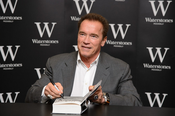 Arnold signing a copy of his book (picture via The Guardian)