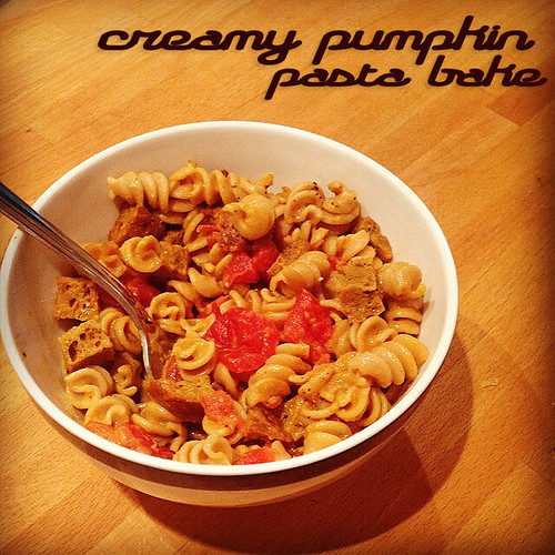 Three-quarter photo of a bowl of spiral pasta with chunks of tomato and fauxsage.