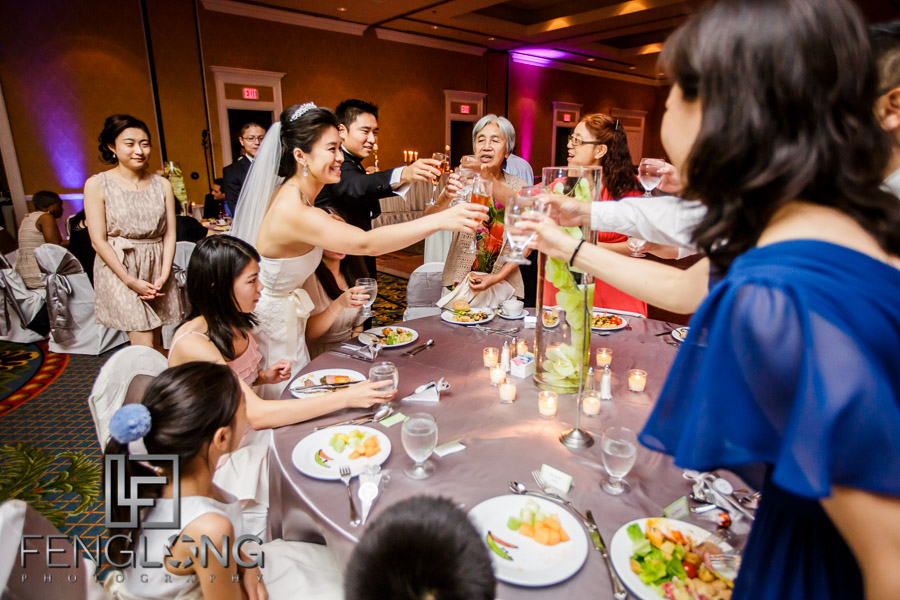 Bride and groom greet guests at tables during the wedding reception