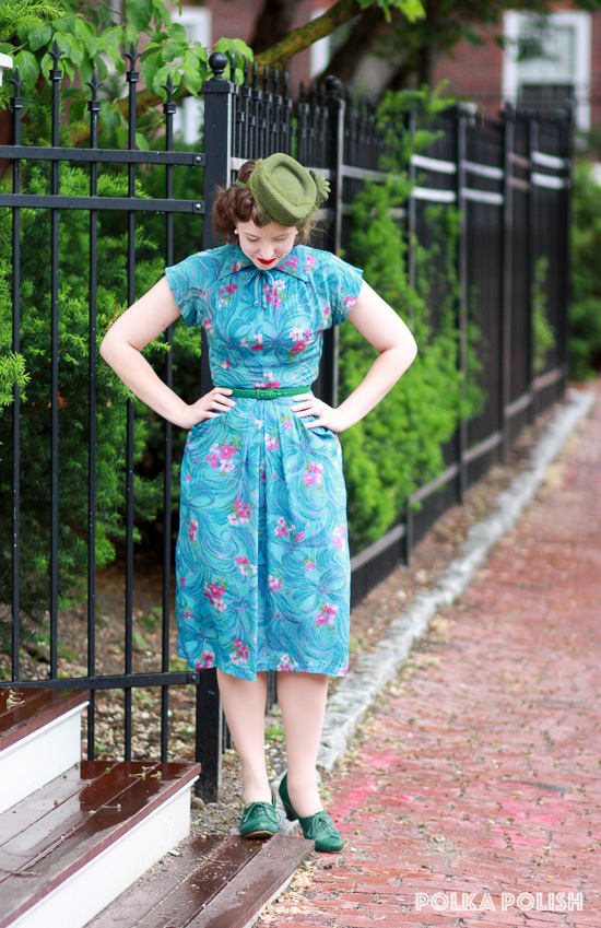 1940s novelty print dress with bows and flowers in shades of pink, olive green, and aqua.  A smart tilt hat in a matching olive color completes the look