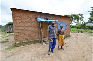 Mr Tembo with his wife in front of the house which he was able to build from the proceeds of his last year's harvest under SIMLEZA-Africa RISING (Photo credit: IITA/Jeffrey Oliver)