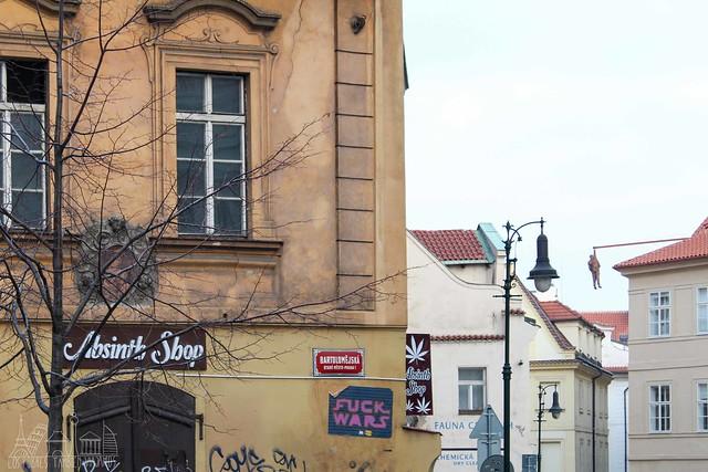 """Fachadas de Praga con un cartel de Absenta, otro en el que reza """"Fuck Wars"""" y, a lo lejos, la escultura de Freud suspendido desde la azotea de un edificio."""