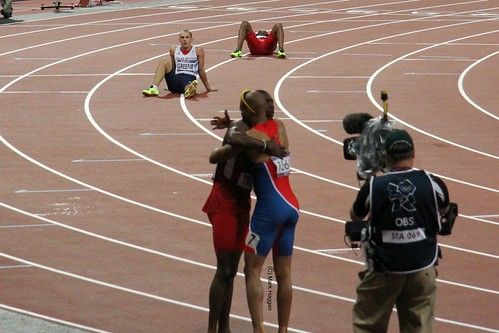Gold and Silver medal winners Felix Sanchez and Michael Tinsley hug after the 400m hurdles as Dai Greene of Team GB, who finished 4th, watches at the London 2012 Olympics