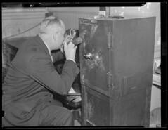 Detective examines fingerprints on blown safe