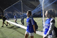 Tomoko Matsumoto, an exchange student from Japan, brings the goal back to the storage area after a game with her new American teammates, San Jose, Calif.