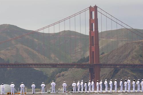 Sailors aboard USS Nimitz man the rails as it passes under the Golden Gate Bridge. by Official U.S. Navy Imagery
