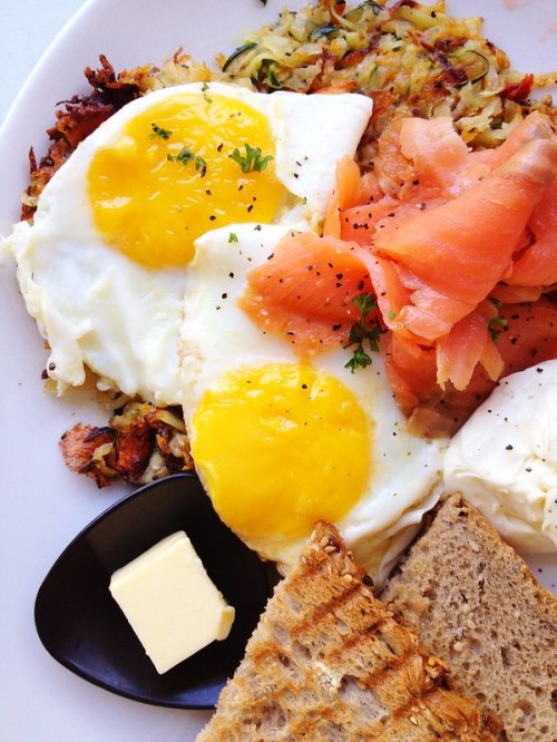 Zucchini rosti with two sunny-side-up eggs, smoked salmon, lemon cream cheese and toast