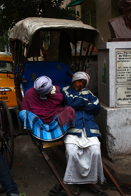 Two rickshaw drivers taking a nap by the street