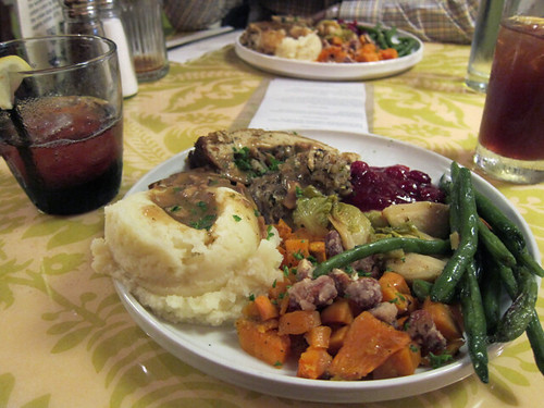 Round white plate filled with green beans, Brussels sprouts, sweet potatoes, mashed potatoes, gravy, stuffing, tofu turkey, and cranberry sauce.