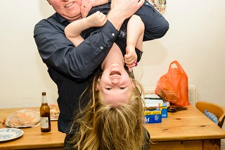 A man holding his little girl upside down -- she's smiling and her hair hangs down.
