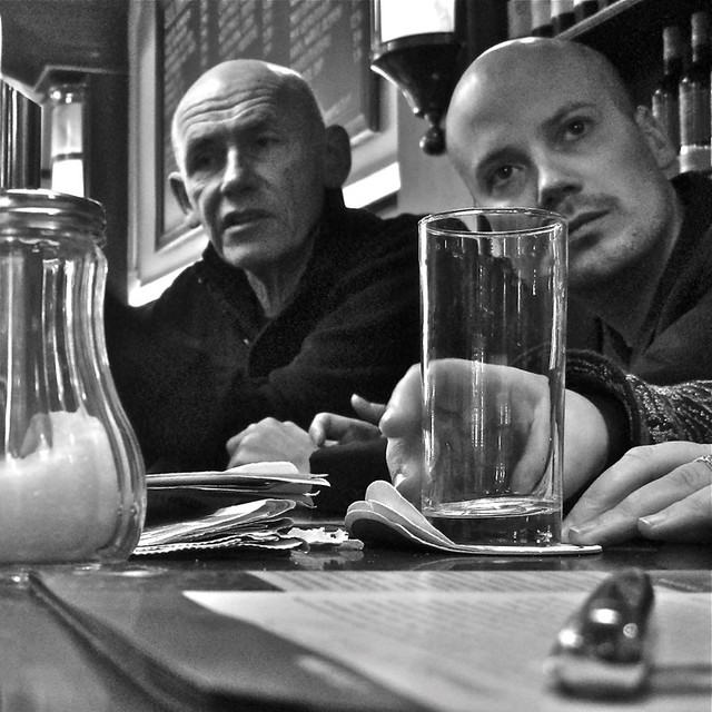 Two bald gentlemen in a cafe