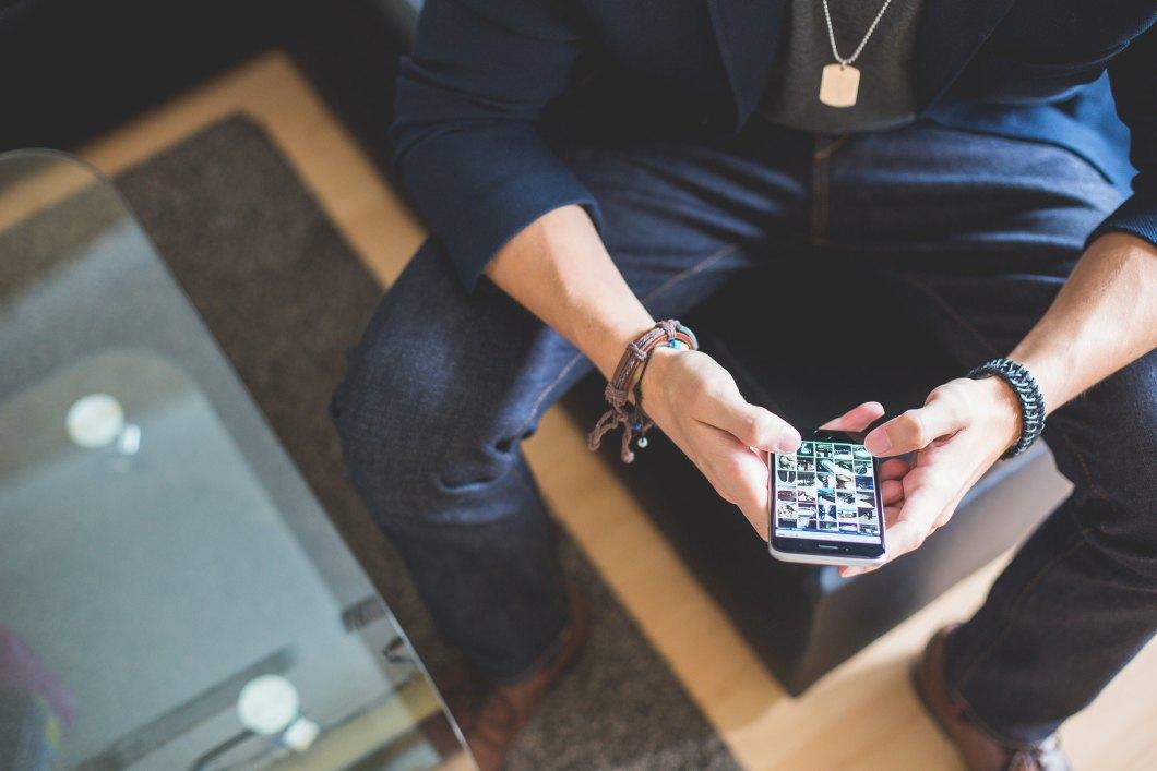 Imagen gratis de un chico navegando con su smartphone