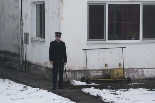 Romanian stationmaster watches our train roll past