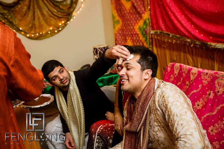 Giving groom henna during Mehndi night at Ismaili wedding
