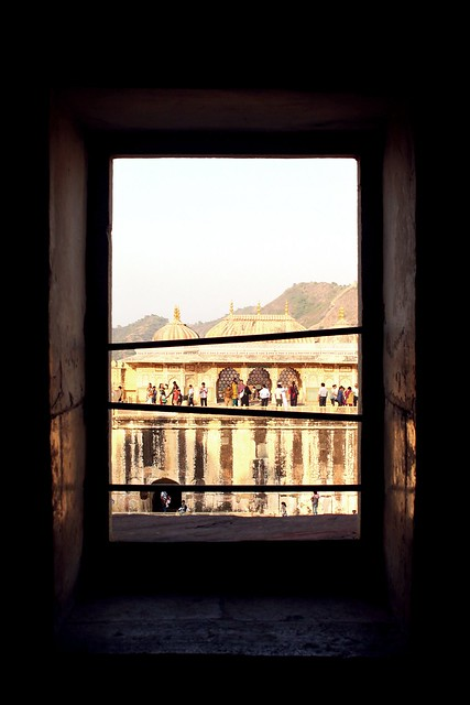 Image: an open window at the Amber Fort in Jaipur. Bars criss-cross the porthole, and people walk around outside.