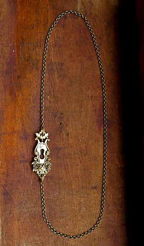 a brass key plate on a brass chain by denise carbonell