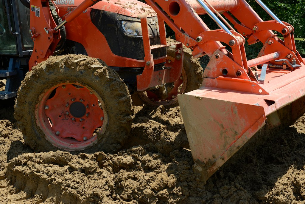 Photograph of Kubota tractor (orange) mixing sand, clay, straw and water to form cob.