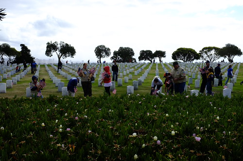 Boy Scouts place flags on headstones at Ft. Rosecrans Cemetery in preparation for the Memorial Day holiday. by Official U.S. Navy Imagery