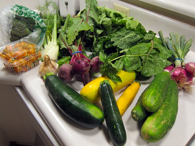 A large pile of veggies on a kitchen counter.