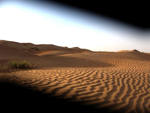 Desert sand ripples through a trapped camera lens