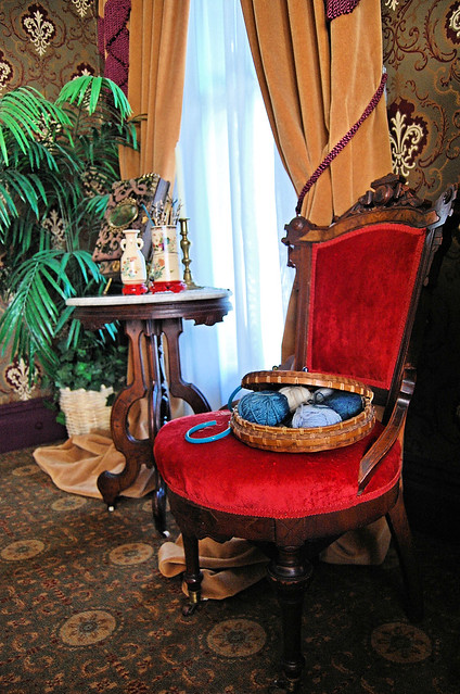 A red velvet chair with a knitting basket full of yarn balls sits next to a marble table.