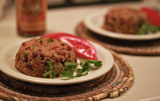 White plate with a small mound of rice and beans next to a sprig of cilantro and a few slices of tomato. In the background is another plate of rice and beans and a jar of hot sauce.