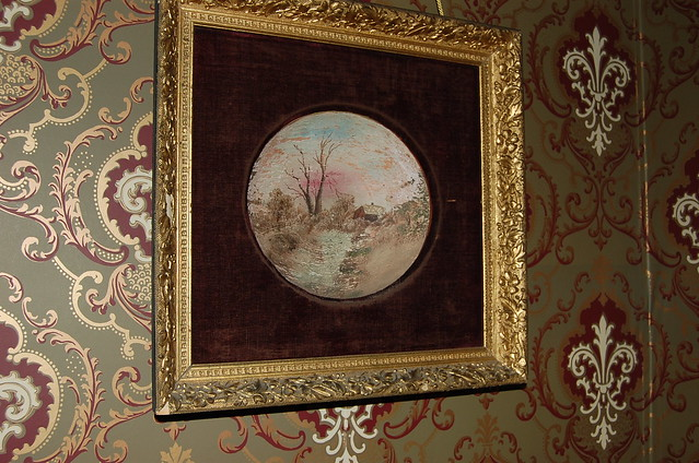 A bowl painted with a fall scene is matted with red velvet and framed with a gold leaf frame