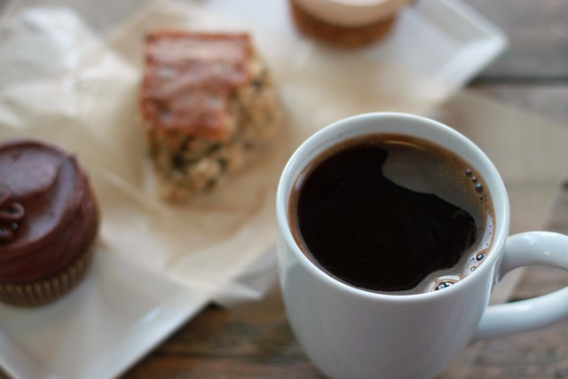 Top-down view of a big mug of coffee in the left-hand side of photo. In the right background is a small white rectangular platter with two cupcakes and a blondie.