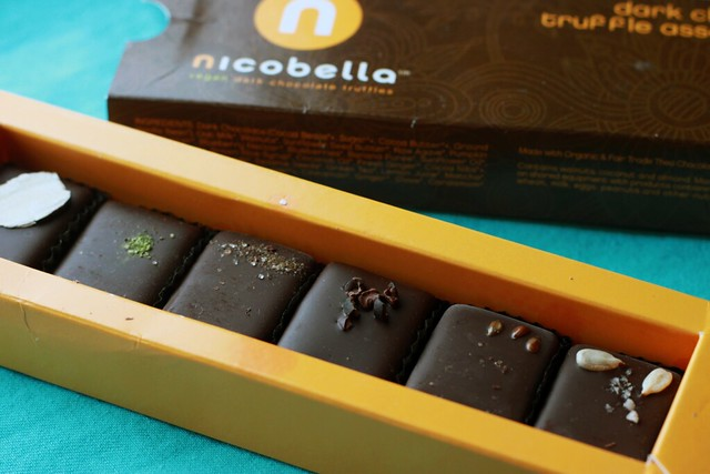 Thin rectangular box filled with six small rectangular truffles.