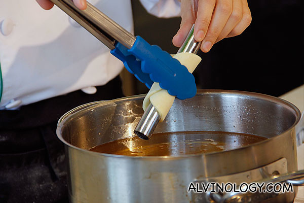 Using a tong to transfer the cannoli into a pot of boiling oil