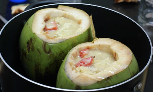 Paneer in Tender coconut shells being simmered in water bath