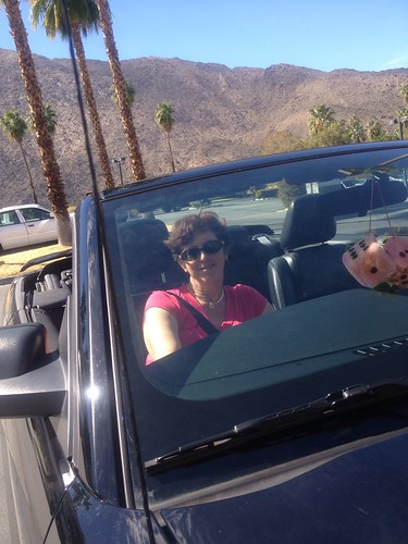In a convertible with pink fuzzy dice, in Palm Springs