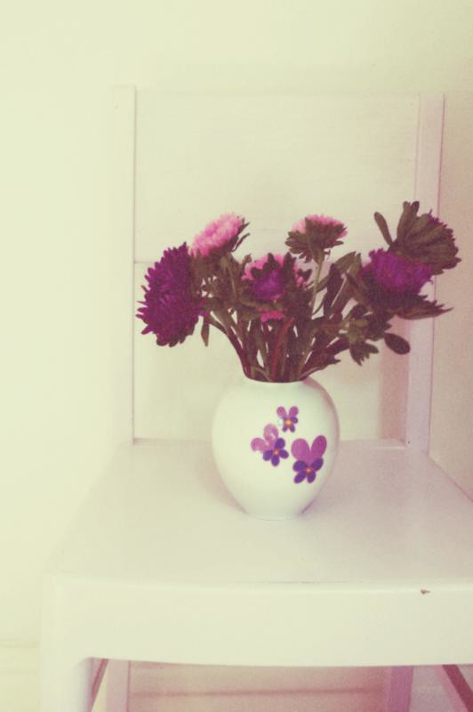 Pink and purple dahlias in vintage vase on kitchen chair