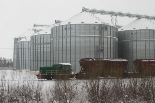 Tiny 0-4-0 diesel shunter at work beside a modern grain silo in Ukraine