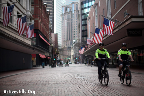 POLICE OFFICER RIDE IN AN EMPTY STREET IN DOWNTOWN BOSTON WHILE BOSTON WAS IN THE LOCKDOWN THAT WAS ANNOUNCED DURING MANHUNT FOR THE SUSPECT IN THE BOMBING OF THE 117TH BOSTON MARATHON ON APRIL 15, 2013. MUCH OF THE BOSTON AREA WAS CLOSED OR IN LOCKDOWN DURING THE INVESTIGATION AND RESIDENTS HAVE BEEN ASKED TO STAY INSIDE. PUBLIC TRANSPORT WAS SUSPENDED IN THE GREATER BOSTON. PHOTO: TESS SCHEFLAN/ACTIVESTILLS.ORG