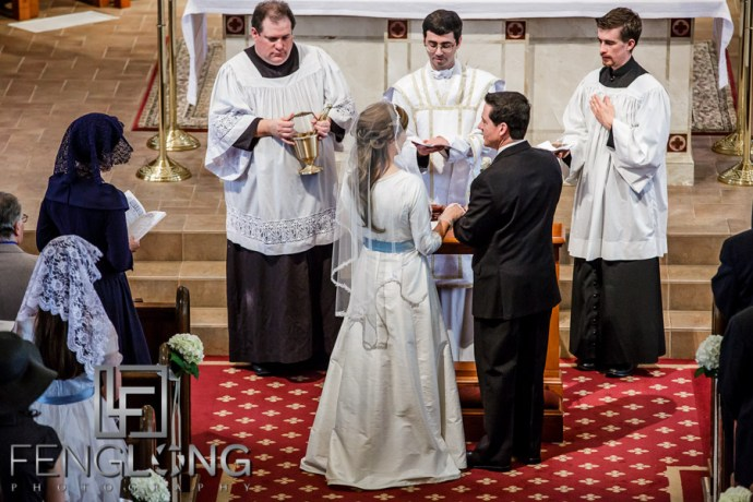 Bride and groom exchanging rings during Catholic ceremony