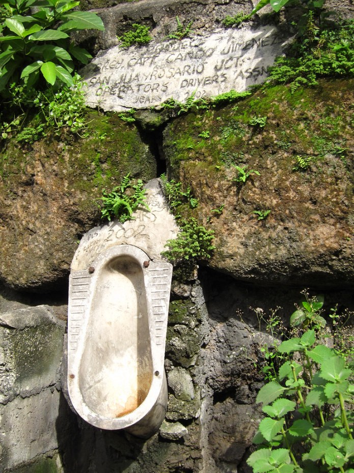 urinal on a stone wall in an alley