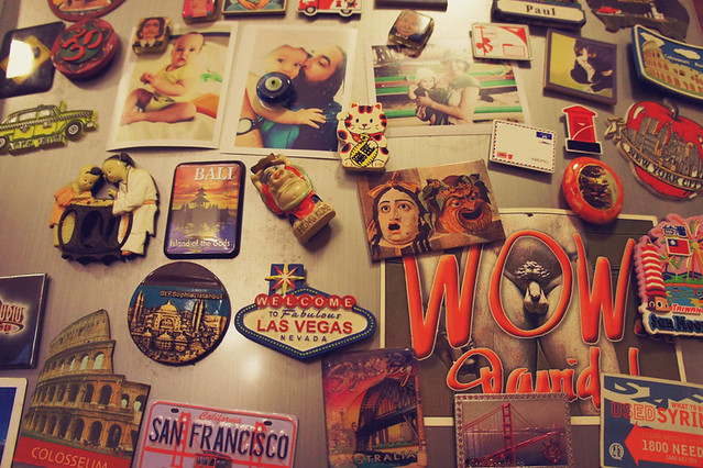 Fridge door with collection of magnets from world travels, postcards from friends and photos