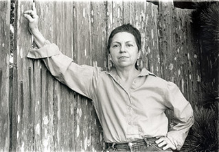 gloria anzaldua with her arm outstretched, leaning on a wooden plank fence