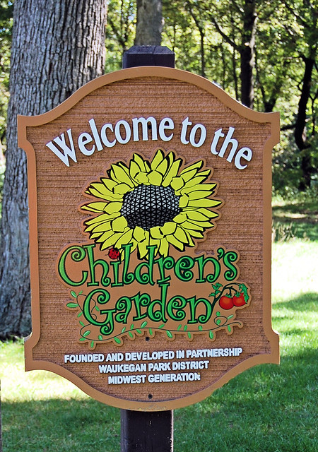 Sign before an area of raised gardens that were planted by children groups