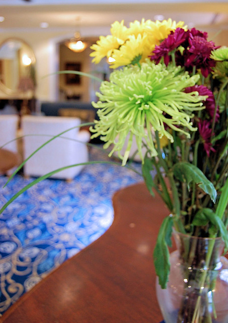 flower arrangement in foreground and blue lobby in background