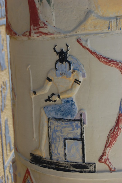a dung beetle faced deity sits on a throne enshrined as Pharaoh the image has been partially painted